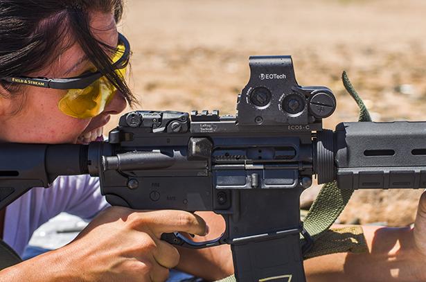 Female shooter fires an AR-15 rifle.